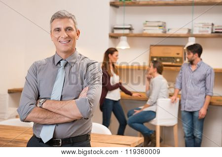 Confident senior businessman keeping arms crossed and standing. Smiling business man with group of business people meeting in office in background. Portrait of a smiling leader looking at camera.