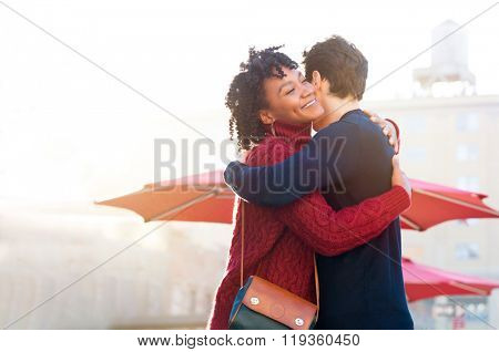 Happy young african woman hugging her friend outside cafe. Attractive young couple embracing each other and smiling. Romantic happy couple hugging outdoor and smiling in a beautiful day.