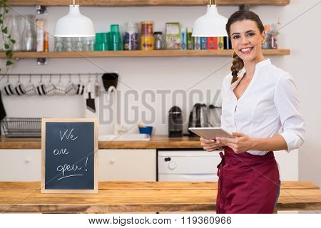Portrait of young happy waitress looking at camera at bar with digital tablet. Portrait of a young female chef with blackboard in kitchen corner. Young smiling woman in her small business shop.
