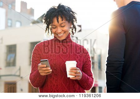 Young woman standing with friend texting on the phone and holding a take away paper cup of coffee. African girl with paper cup writing text message with smart phone while walking on road.