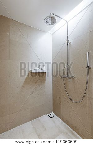 Shower cabin in modern bathroom interior in beige color