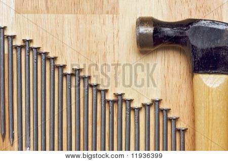 Hammer and Declining Graph of Nails Abstract on Wood Background.