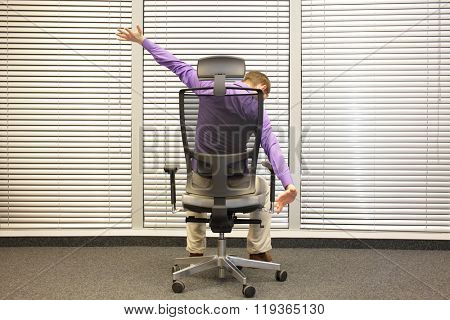 man  stretching arms sitting on chair in office  -  back view