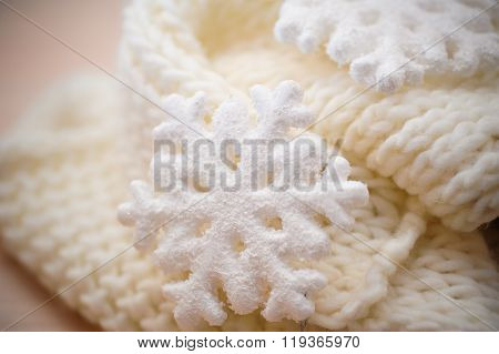 Big white snowflake on white knitted scarf background
