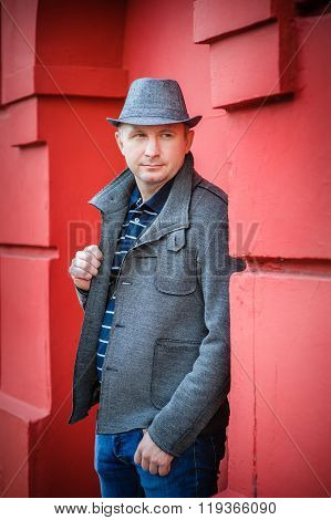 man in a hat near the red wall