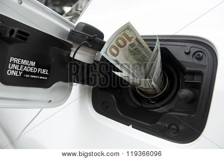 One hundred dollars USD worth of twenty dollar bills sticking out of a car gas cap.