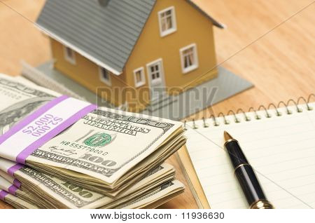 House and Money with Pad of Paper and Pen