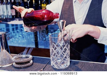 Bartender is pouring black currant shrub in mixing glass, toned image