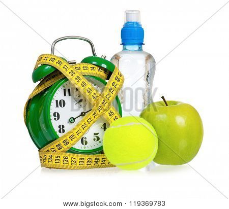 Big green alarm clock with tennis ball and bottle of water, isolated on white background