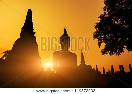 Ancient Buddha Statue at sunset Sukhothai historical park, Mahathat Temple ,Thailand.
