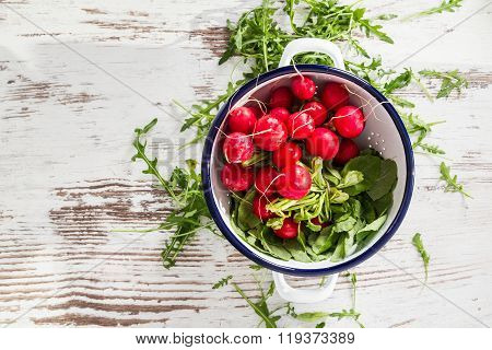 Top View On Fresh Wet Radishes In White Colander Over Old Wooden Table