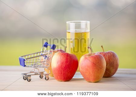 apples, apple juice and a shopping cart on a wooden table, outdoor