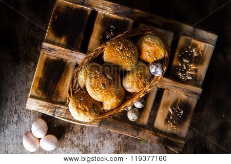 Easter Eggs With Kaiser Rolls And Sesame Seeds On Retro Crate. Top View