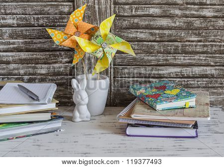 Children's Home Workspace With Books, Notebooks, Notepads, Tablet And Handmade Paper Pinwheels And E