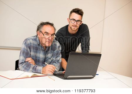 Young Man Teaching Eldery Man Of Usage Of Computer. Intergenerational Transfer Of Computer Skills.