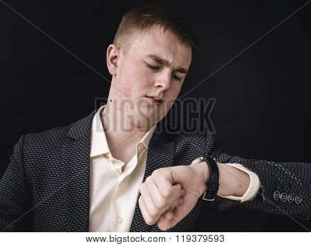 Businessman looking at the time on his wrist watch against dark background.