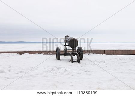 Old cannon on a winter embankment