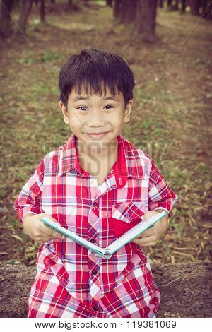 Asian Boy Smiling And Holding A Book. Education Concept. Vintage Style.