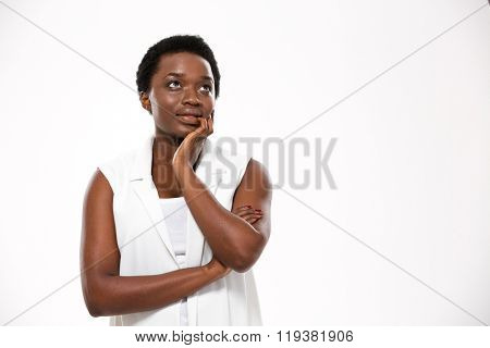 Pensive attractive african american young woman standing and dreaming over white background