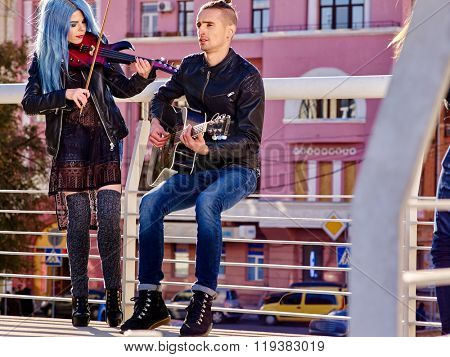 Music street performers girl violinist and man guitarist on urban background outdoor.