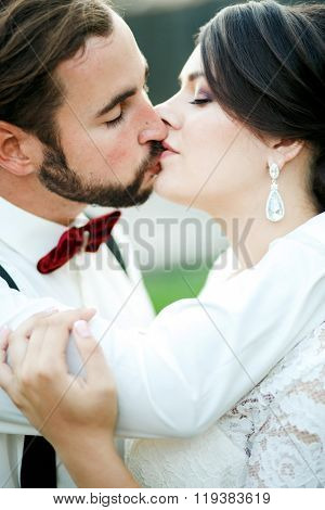 Bride and groom kissing. Wedding couple, newlyweds kiss. Close portrait. The man in bow tie with sus