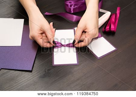 Woman Tying A Bow On A Handmade Card