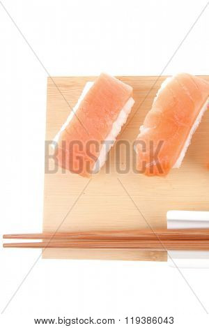 Japanese Cuisine - Set of Nigiri sushi topped with raw Salmon . on wooden board . isolated over white background