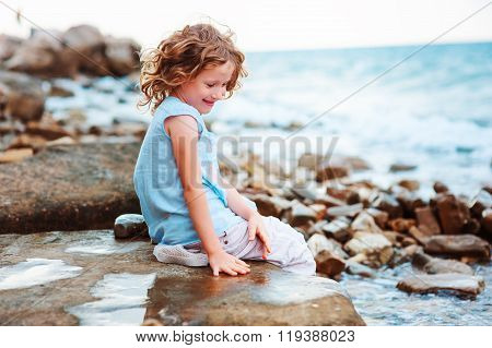 happy kid girl playing with water on the stone beach. Cozy vacation on sea, traveling with kids.