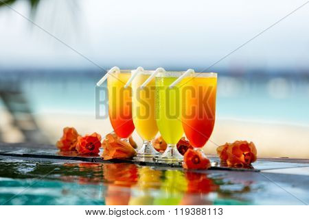 Fresh summer cocktails drinks placed next to swimming pool with ocean on background.
