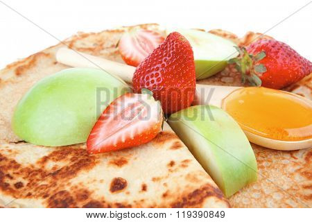 sweet food big thin pancake with honey strawberries and apple isolated over white background