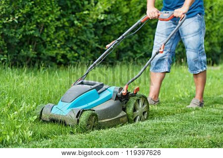 Man Mowing The Lawn With Blue Lawnmower In Summertime