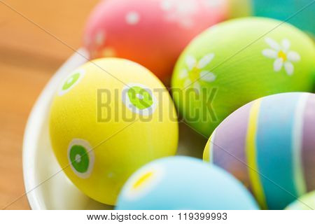 easter, holidays, tradition and object concept - close up of colored easter eggs on plate
