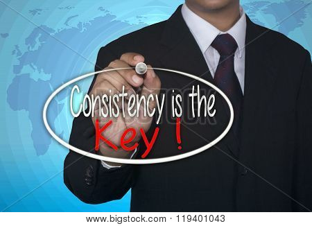 Business concept handwriting marker and write Consistency is The Key over light blue background with
