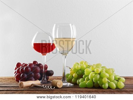 Wine and grape on wooden table against light background