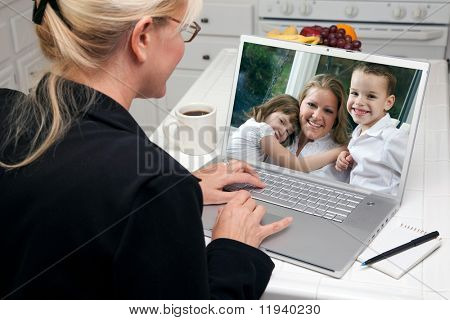 Woman In Kitchen Using Laptop See Friends and Family. Screen image can easily be replaced using the included clipping path.