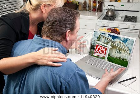 Couple In Kitchen Using Laptop to Research Real Estate. Screen image can easily be replaced using the included clipping path.