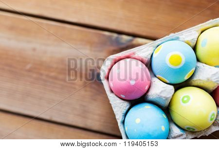 easter, holidays, tradition and object concept - close up of colored easter eggs in egg box or carton wooden surface with copy space