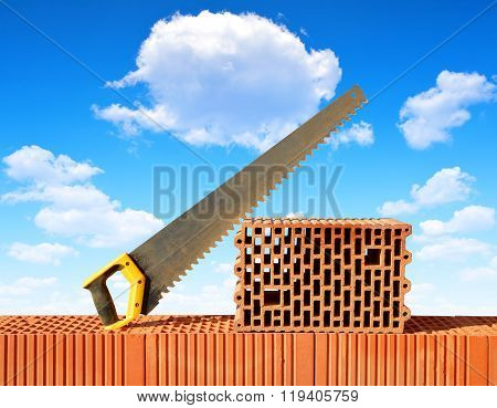 Brick wall with handsaw on bricks