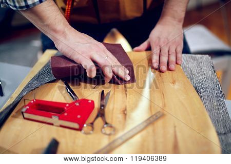 Carpenter sanding plank in his workshop