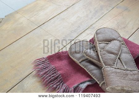 Old leather mittens and scarf on wood table