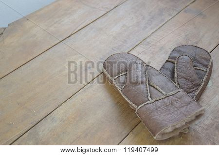 Old leather mittens on wood table
