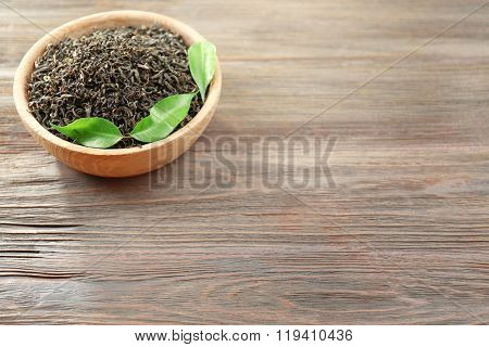 Dry tea with green leaves in bowl on wooden table background, copy space