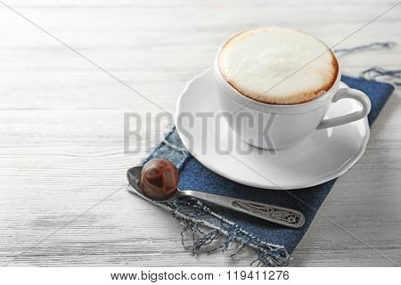 Cup of hot cappuccino with froth and candy on white wooden table table