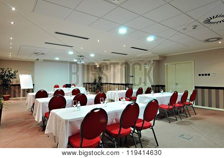 Empty white conference room with red armchairs