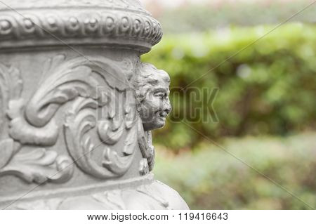 Fragment of decorative head column sculpture on a blurred background