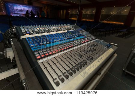 Professional music mixer console with faders and adjusting knobs close up