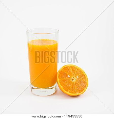 The glass of tasty pure orange juice and fresh orange half