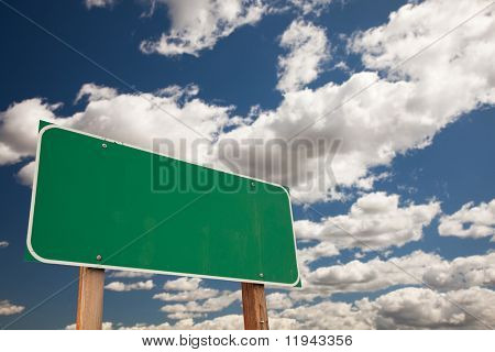 Blank Green Road Sign on Dramatic Blue Sky with Clouds - Plenty of Room For Your Own Text in the Clouds and on the Large Sign.