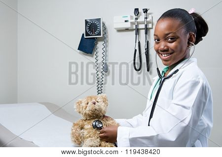 Girl doctor using stethoscope on teddy bear