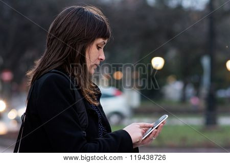 Brunette Woman Using Smart Phone In City